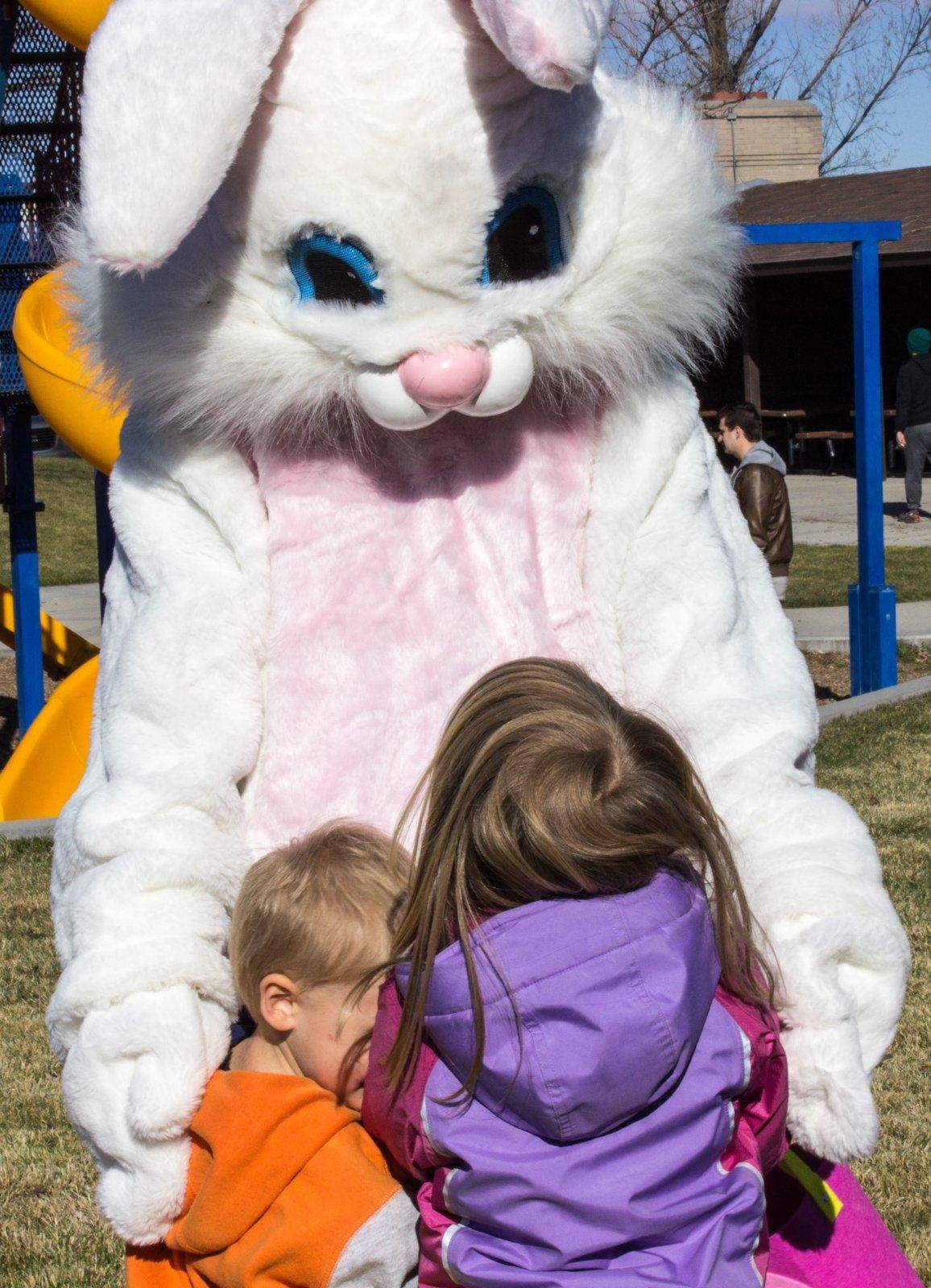 The Easter Bunny hugging children.