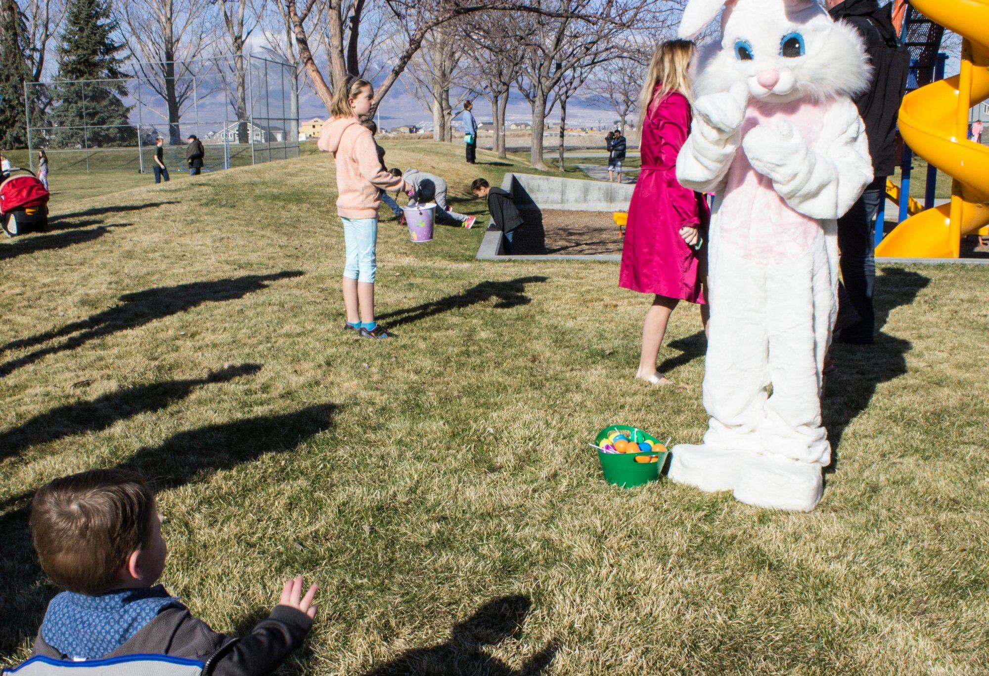 The Easter Bunny waving to a child.